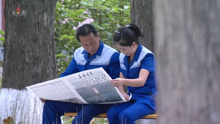 This Oct. 4 photo, released by North Korea's state-run Korean Central Television (KCTV) shows North Korean residents reading the country's ruling Workers' Party of Korea (WPK) newspaper Rodong Sinmun Oct. 3 edition which highlighted the North's test launch of its new Pukguksong-3 submarine-launched ballistic missile (SLBM) off the coast of Wongsan, Kangwon Province, the day before. KCTV-Yonhap