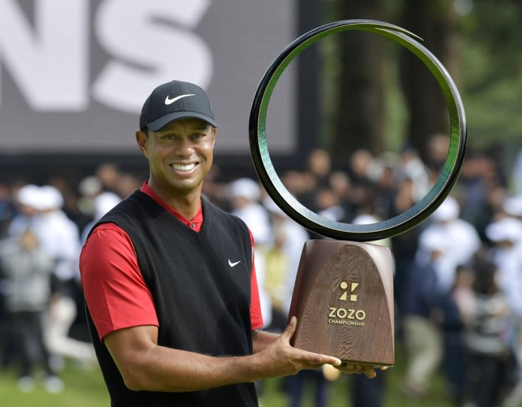 Tiger Woods holds a winning trophy as he celebrates to win the Zozo Championship, a PGA Tour event, at Narashino Country Club in Inzai, Chiba Prefecture, east of Tokyo, Japan, Monday. /Reuters-Yonhap
