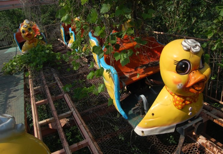 The duck sky cycle ride is covered in vines at Okpo Land, an abandoned amusement park on Geoje Island, in 2008. / Courtesy of Ron Bandun