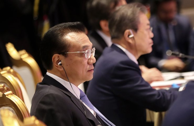 Chinese Premier Li Keqiang, left, and President Moon Jae-in wait to speak at the Association of Southeast Asian Nations (ASEAN) Plus Three summit in Nonthaburi, Thailand, Nov. 4. AP-Yonhap