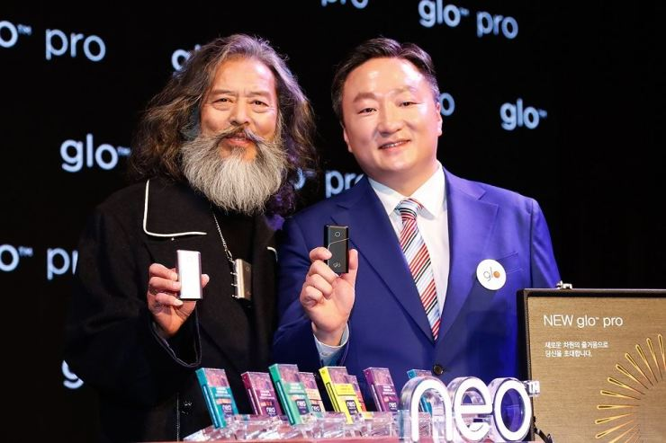 BAT Korea CEO Kim Eui-soung, right, introduces the glo pro tobacco heating device during a launch event at Lotte Hotel in downtown Seoul, Tuesday. On left is model Kim Chil-doo. Courtesy of BAT Korea