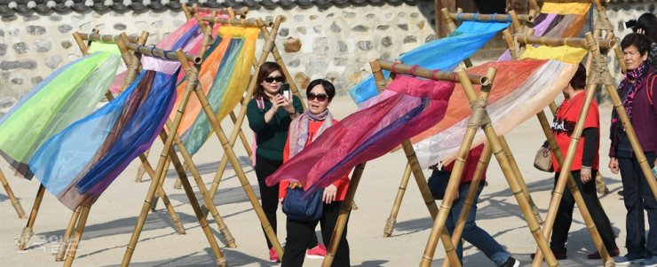 Tourists look at art installations made of the skirts of hanbok, traditional Korean garments, at Namsangol Hanok Village in Seoul, Tuesday. The installations are part of the 'Hang in Hanok' exhibition. / Korea Times photo by Bae Woo-han