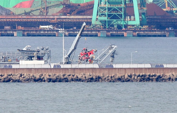 The fuselage of a destroyed rescue helicopter, which crashed into the sea Thursday, is moved to a special carrier at a port in Pohang, North Gyeongsang Province, Monday. Yonhap