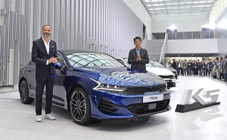 Kia Motors Design Center Head Karim Habib, left, and Vice President Kwon Hyuk-ho pose with the new K5 during an unveiling event in Yongin, Gyoneggi Province, Thursday. The third generation K5 is available with gasoline, LPG and hybrid powertrains. Priced start from 23.51 million won and the company has begun receiving pre-orders with the goal of selling 70,000 by the end of next year. Courtesy of Kia Motors