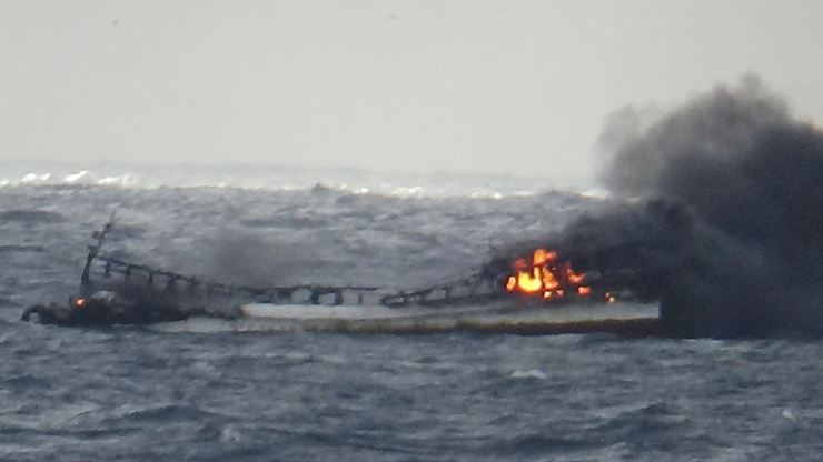 A fishing boat is seen on fire in seas west of Jeju Island, Tuesday. One of the 12-man crew was found dead by the Coast Guard, which is conducting search and rescue operations for the other 11. Courtesy of Mokpo Coast Guard