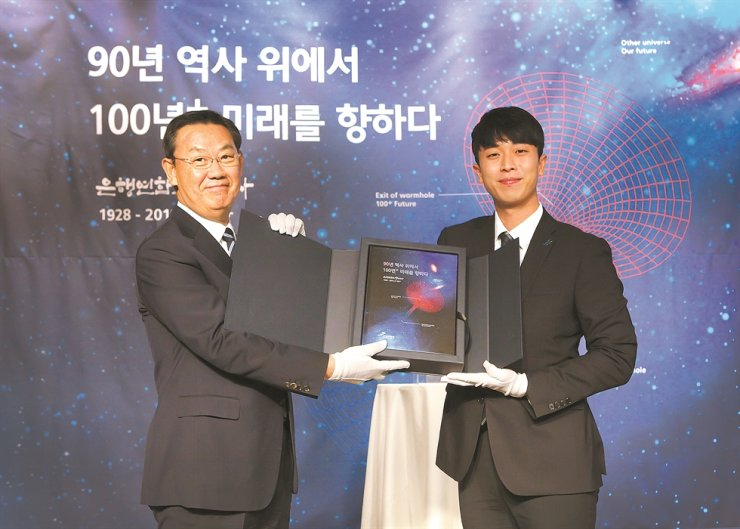 Korea Federation of Banks (KFB) Chairman Kim Tae-young, left, holds a book published to celebrate the 90th anniversary of the organization at the KFB headquarters in Seoul, Nov. 1. Courtesy of KFB