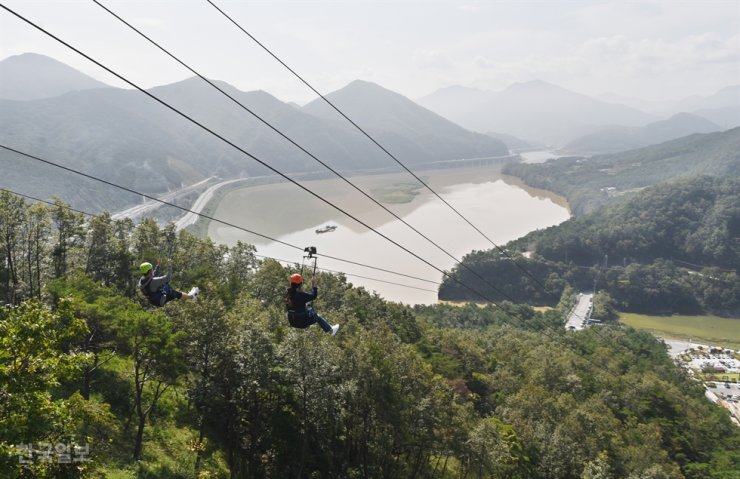 People ride a zip line in Damyang, South Jeolla Province, last month. One Korean tourist was killed and two others were injured while zip lining in Laos, Tuesday. Korea Times photo by Choi Heung-soo