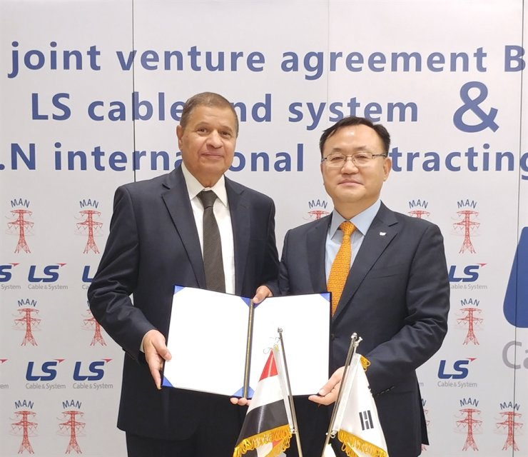 LS Cable & System CEO Myung Roe-hyun, right, poses with Mohamed Ali Abdellah, chairman of Egyptian cable-laying company M.A.N International Contracting, after signing a contract to set up a joint venture in Cairo, Nov. 20. LS said the joint venture will build a production facility by the end of 2020 to produce overhead transmission wires. / Courtesy of LS C&S
