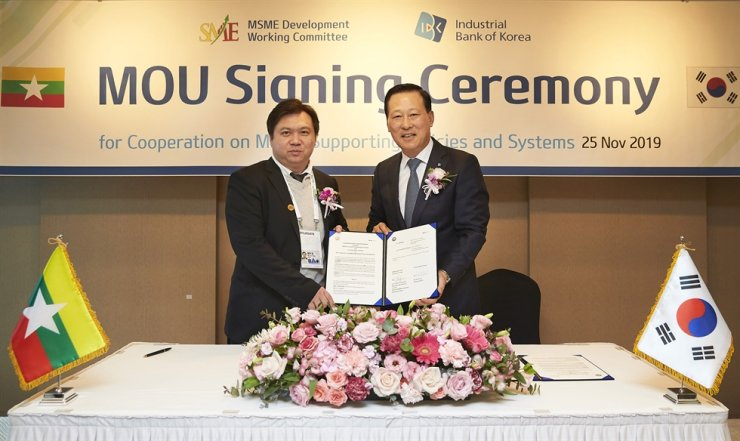 Industrial Bank of Korea (IBK) CEO Kim Do-jin, right, poses with Myanmar's Ministry of Industry Deputy Minister Min Ye Paing Hein after signing a memorandum of understanding to boost cooperation in supporting SMEs at Lotte Hotel Busan, Nov. 25. Courtesy of IBK