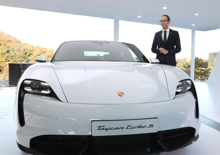 Porsche Korea CEO Holger Gerrmann with the electric Porsche Taycan Turbo S at an unveiling event at the Banyan Tree Club & Spa in Seoul, Friday. The Taycan will be officially launched in Korea in the second half of next year. Yonhap