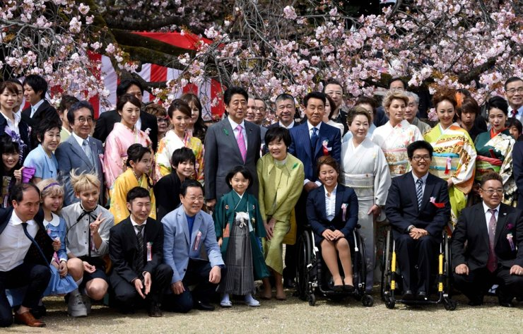 This file photo taken on April 15, 2017 shows Japan's Prime Minister Shinzo Abe (centre L) and his wife Akie (centre R) posing with entertainers and athletes during the cherry blossom viewing party hosted by the prime minister in Tokyo. AFP