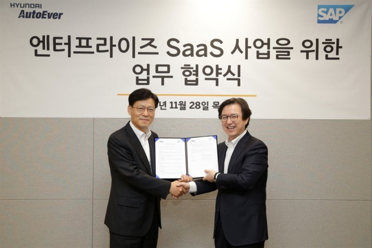 Lee Sung-youl, right, managing director of SAP Korea, poses with Oh Il-seok, CEO of Hyundai AutoEver, after signing a memorandum of understanding to develop and operate cloud-based enterprise software at the latter's headquarters in Seoul, Thursday. / Courtesy of SAP Korea