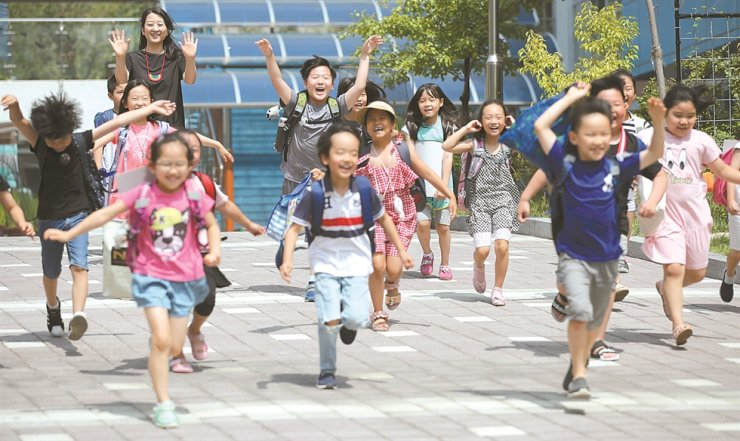 Elementary students in Seoul jump for joy after the school officially announces its summer break in this July 19 photo. /Korea Times file