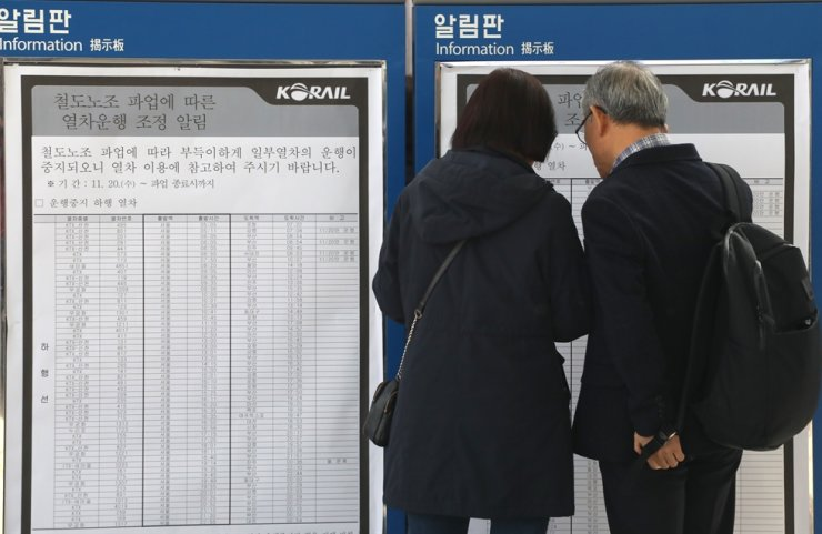 People check the revised schedule for passenger trains at Seoul Station, Friday, the third day of the railway workers' indefinite strike. / Yonhap