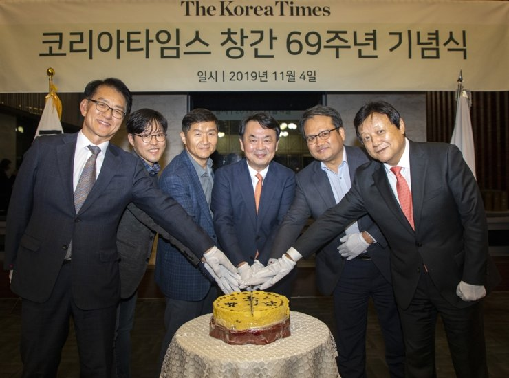 Lee Byeong-eon, third from right, president-publisher of The Korea Times, and Lee Jun-hee, right, president of the English daily's sister paper, the Hankook Ilbo, take part in a cake cutting ceremony, along with other officials from the two newspapers, during an event held in Seoul, Monday, to mark The Korea Times' 69th anniversary. / Korea Times photo by Shim Hyun-chul