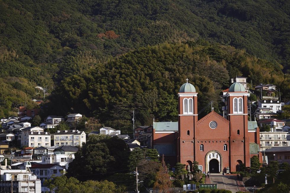 In this Nov. 16, 2019, photo, a woman walks by a poster of Pope Francis at the Urakami Cathedral in Nagasaki, southern Japan. AP-Yonhap