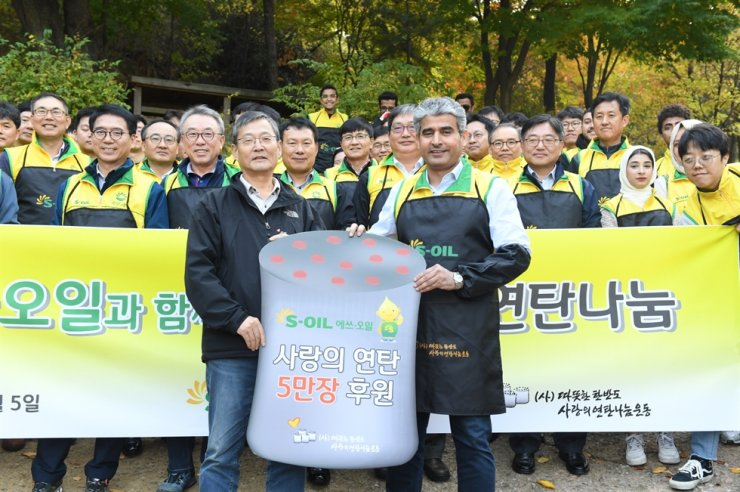 S-Oil CEO Hussain Al-Qahtani, right, poses for a photo with Coal Briquettes for Neighbors in Korea Director Lee Dong-seob, left, and 60 employees in an impoverished neighborhood in Hongje-dong, Seoul, Tuesday. The company delivered coal briquettes to low-income residents in Seoul. / Yonhap