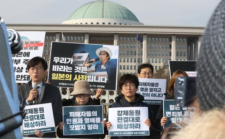 Civic activists and lawyers hold a press conference in front of the National Assembly in Seoul, Wednesday, condemning Assembly Speaker Moon Hee-sang's idea for compensating wartime forced laborers through a joint fund pooled by Japanese and Korean companies. / Yonhap
