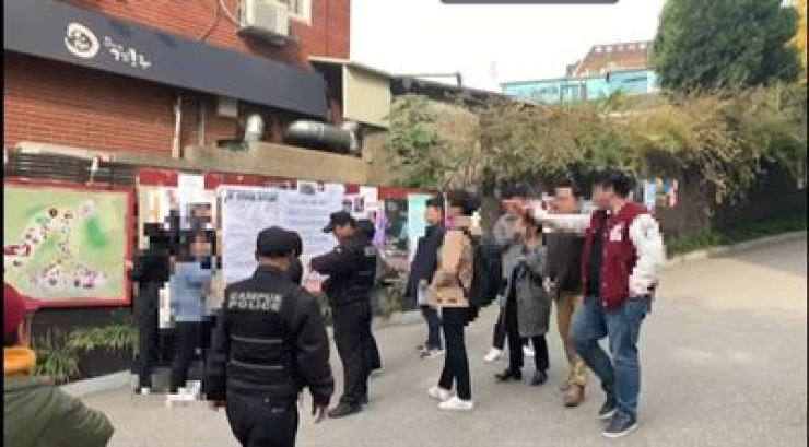 Korean students from Korea University argue with Chinese students on the university campus in Seoul, Tuesday, as the latter try to remove banners showing support for pro-democracy protests in Hong Kong. / Korea Times photo by Kim Young-hoon