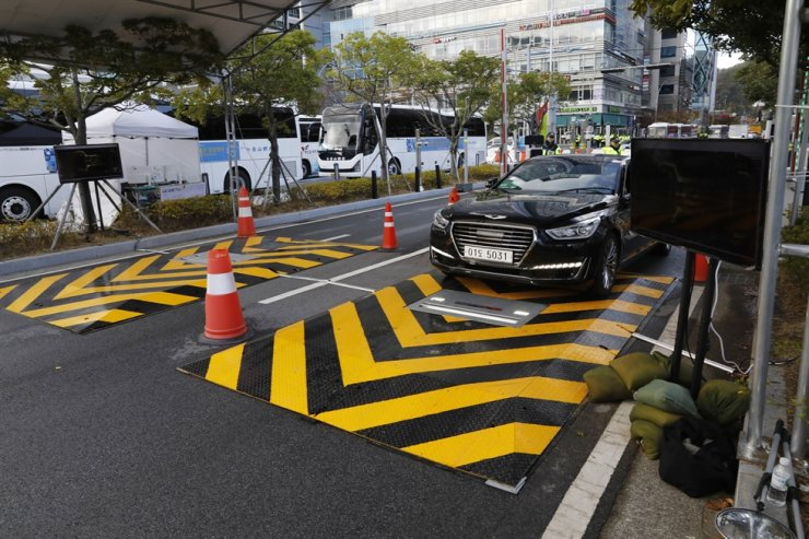 A car passes over the Under Vehicle Surveillance System which scans its underbody, at the entrance to BEXCO in Busan, the main venue of the 2019 ASEAN-Republic of Korea Commemorative Summit, Tuesday. The system, developed by D&S Technology, detects prohibited items hidden under vehicles. / Korea Times photo by Shim Hyun-chul