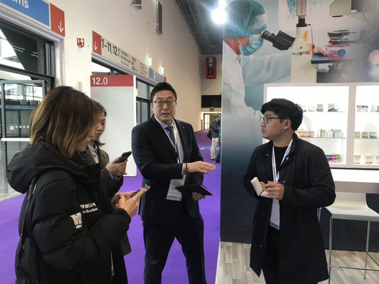 Samsung BioLogics' head of global business development James Park, center, talks to reporters at the company's booth at the 2019 Convention on Pharmaceutical Ingredients (CPhI) Worldwide in Frankfurt, Tuesday (local time). Korea Times photo by Nam Hyun-woo