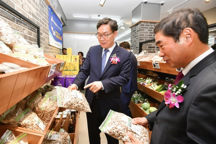 NongHyup Bank CEO Lee Dae-hoon, left, looks at items sold at the lender's second branch that opened inside a NongHyup Hanaro Mart in Chuncheon, Gangwon Province, Nov. 14. / Courtesy of NongHyup Bank