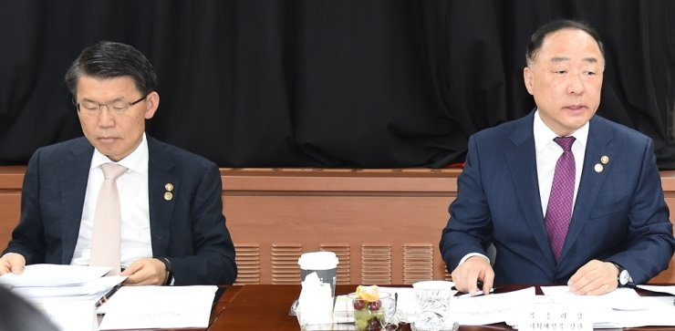 Deputy Prime Minister and Finance Minister Hong Nam-ki, right, and Financial Services Commission Chairman Eun Sung-soo attends a ministers' meeting at the Government Complex Seoul in this Nov. 14 file photo. Both Hong and Eun were absent from the Korea-ASEAN Commemorative Summit in Busan. / Yonhap