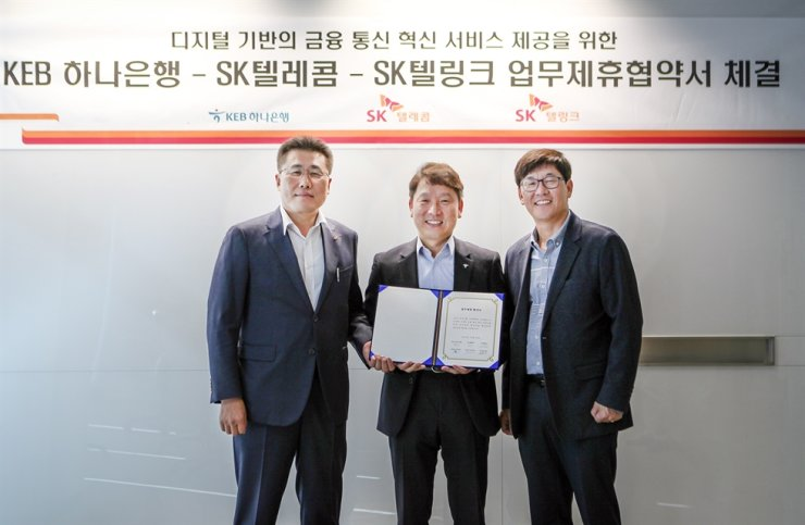 KEB Hana Bank's head of future finance projects Yeom Jeong-ho, center, poses with SK Telink CEO Kim Sun-jung, left, and SK Telecom's head of sales Kim Sung-soo after the three signed an agreement to collaborate on developing innovative services in the finance and telecommunications sector, at the SK Telecom's office in central Seoul, Thursday. / Courtesy of KEB Hana Bank