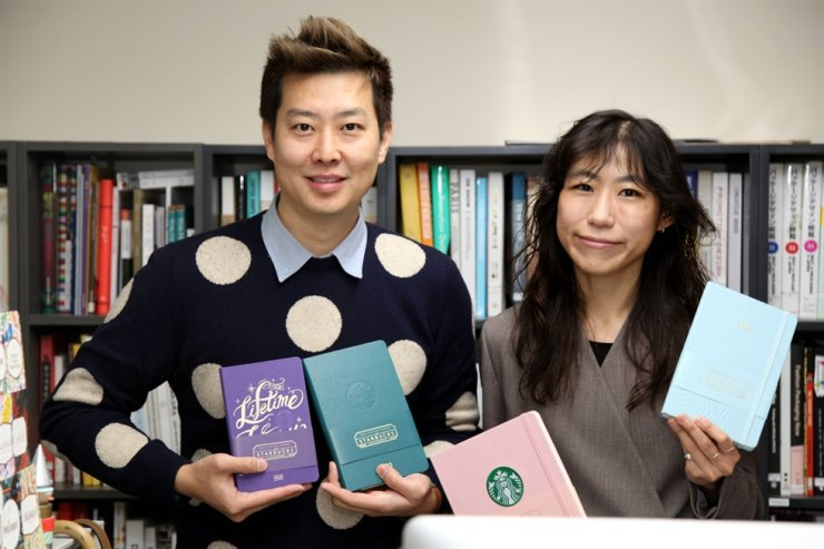 In this photo provided by Starbucks Coffee Korea, planner designers Park Young-ha, left, and Whang So-youn of the creative team pose for a photo with the 2020 planners. Courtesy of Starbucks Coffee Korea