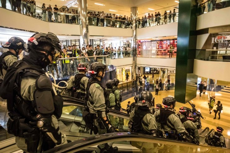Riot police descend an escalator inside the City Plaza mall in the Tai Koo Shing area in Hong Kong on November 3, 2019, after a bloody knife fight wounding six people triggered there. AFP