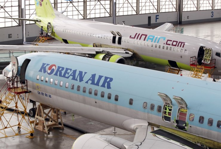 Maintenance officers replace the pickle fork, a part used to connect the wing and aircraft body, on both Korean Air and Jin Air's Boeing B737NGs planes at a Korean Air hangar in western Seoul, Monday. Yonhap