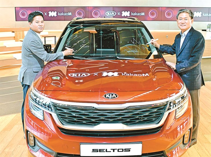 Kia Motors Executive Vice President Kim Sang-dae, left, and Kakao M CEO Kim Sung-soo pose for a photo with a Kia Seltos compact SUV at BEAT360 in Seoul, Tuesday. The two signed a partnership agreement to sponsor the Melon Music Awards (MMAs) 2019 and strengthen cultural marketing promotions. The Seltos, released in July, will be displayed at the MMAs. / Courtesy of Kia Motors