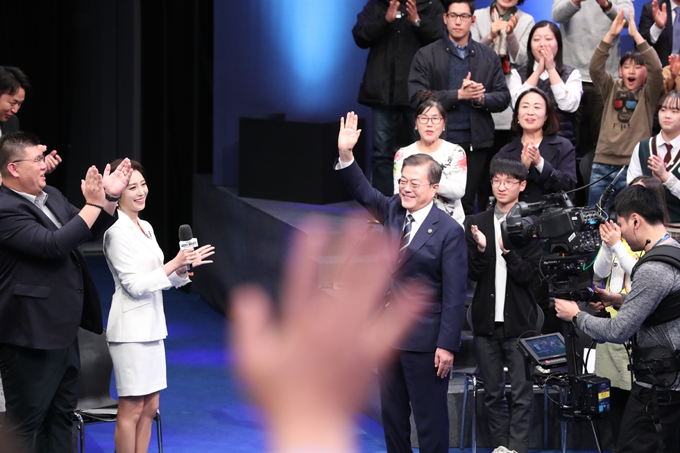 President Moon Jae-in gestures at the start of a nationally-televised live town hall meeting with 300 citizens aired by local broadcaster MBC from its news center in Mapo, Seoul, Tuesday. On Moon's left is Bae Chul-soo, the host of the meeting. No pre-submitted questions were used as the President took random ones, according to Cheong Wa Dae. Yonhap