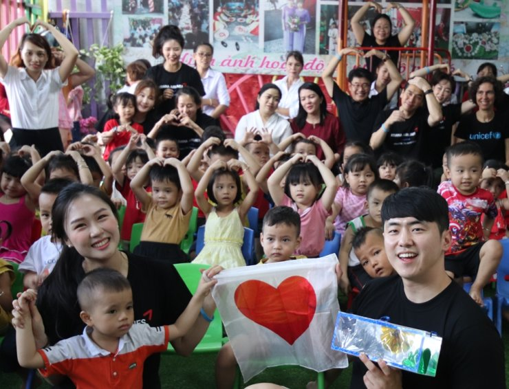 Employees of Asiana Airlines and UNICEF pose with children at Thao Nguyen Xahn Center, a childcare facility in Ho Chi Minh City, Vietnam, Tuesday. The carrier and UNICEF Korea have been aiding some 300 children in four such centers in the city, with Asiana offering 150 million won to them in 2017 and raising another 300 million won, along with UNICEF, through donations of foreign currencies from passengers who finished their trips and didn't need the foreign money anymore. / Courtesy of Asiana Airlines