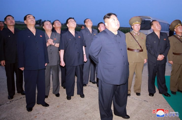 North Korean leader Kim Jong-un, front, watched the regime's new tactical guided missile firing on Tuesday, according to the Korean Central News Agency, in August 2019. Yonhap