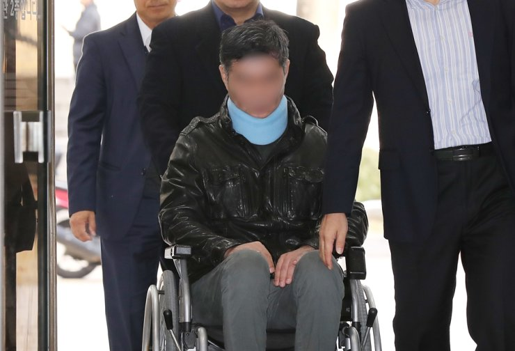 The younger brother of former Justice Minister Cho Kuk in wheelchair enters into the Seoul Central District Court on Thursday to attend a hearing that will decide his arrest. Yonhap