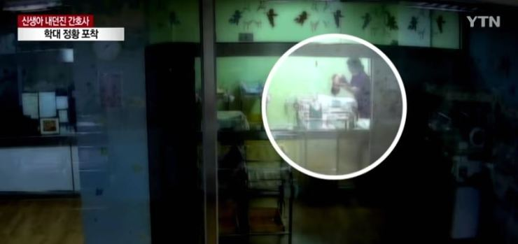 Surveillance video footage shows a nurse holding the legs of a baby while its head hangs down at a gynecology clinic in Busan on Oct. 20. Captured from YTN