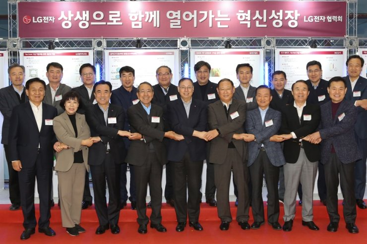 LG Electronics CEO Jo Seong-jin, front row fifth from left, holds hands with partner firm CEOs during a workshop in Pyeongtaek, Gyeonggi Province, Thursday. During the workshop, attended by executives from 95 suppliers, Jo said LG Electronics will support partner firms' automation of manufacturing lines and digitization for mutual growth. Courtesy of LG Electronics