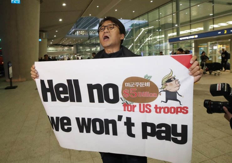 A member of a civic group protests the U.S. government's call for higher payment for stationing American forces on the Korean Peninsula at Incheon International Airport, Sunday, as James DeHart, chief U.S. negotiator in defense cost-sharing talks with Korea, arrives in Korea. / Yonhap