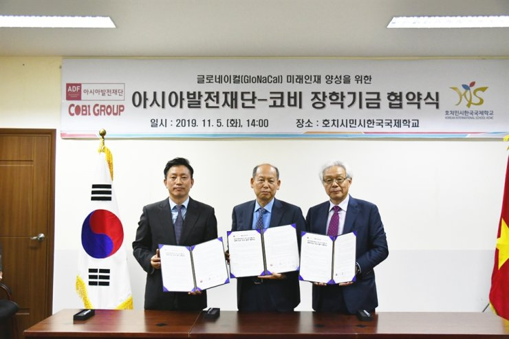 Asia Development Foundation and COBI Group Chairman Kim Joon-il, center, with Korean International School Principal Shin Sun-ho, left, and ADF Vice President Cho Nam-chul at the school in Ho Chi Minh City, Tuesday, after signing an MOU to provide $500,000 in scholarships. / Courtesy of ADF