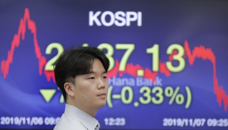 A currency trader walks by a screen showing the Korea Composite Stock Price Index (KOSPI) at the foreign exchange dealing room in Seoul, Nov. 7. Asian stocks are mostly lower after a meandering day of trading left U.S. stock indexes close to their record highs. AP-Yonhap