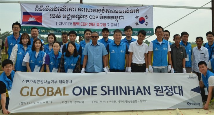 Shinhan Bank employees pose before a groundbreaking ceremony for a football field in a small town in Cambodia's southwestern province of Takeo, Cambodia, Nov. 11. Shinhan officials engaged in a weeklong overseas volunteer program there from Nov. 10, as part of the company's corporate social responsibility activities. Courtesy of Shinhan Bank