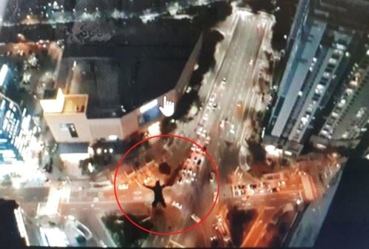 A Russian BASE jumper jumps out of a high rise in Busan, Saturday, in this YouTube captured image. / Yonhap
