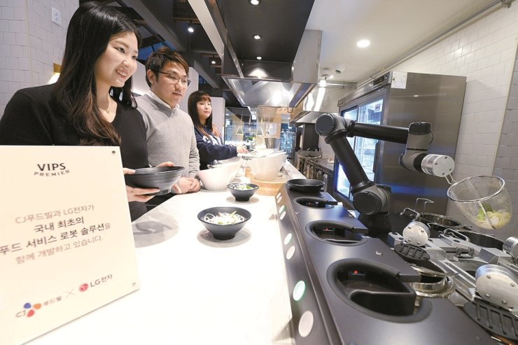 Customers wait for LG Electronics' CLOi Chefbot to cook noodles at a VIPS restaurant in western Seoul, Nov. 22. / Courtesy of LG Electronics