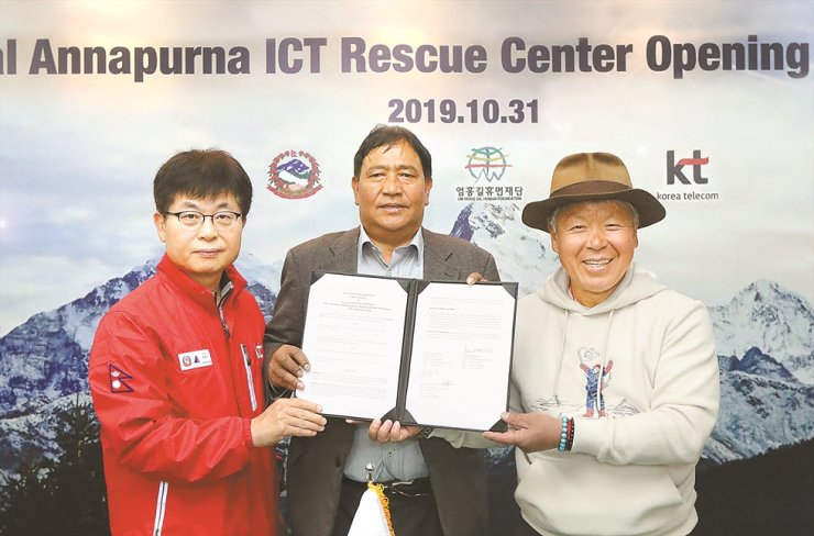 Yoon Jong-jin, left, senior executive vice president of KT, poses with Santa Bir Lama, center, president of Nepal Mountaineering Association, and mountaineer Um Hong-gil at a base camp in Annapurna in the Himalayas, Nepal, after opening an ICT-based rescue center there, Oct. 31. / Courtesy of KT