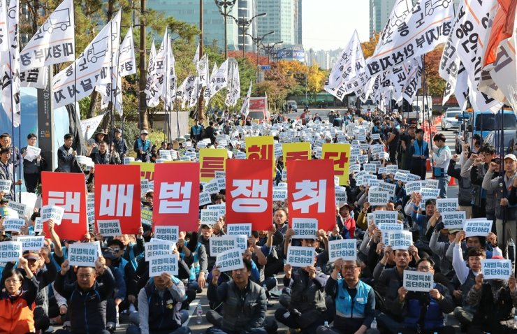 Parcel delivery workers call for the passing of a new law designed to guarantee them better labor conditions and a more stable job status, during a rally in front of the National Assembly in Seoul, Monday. / Yonhap