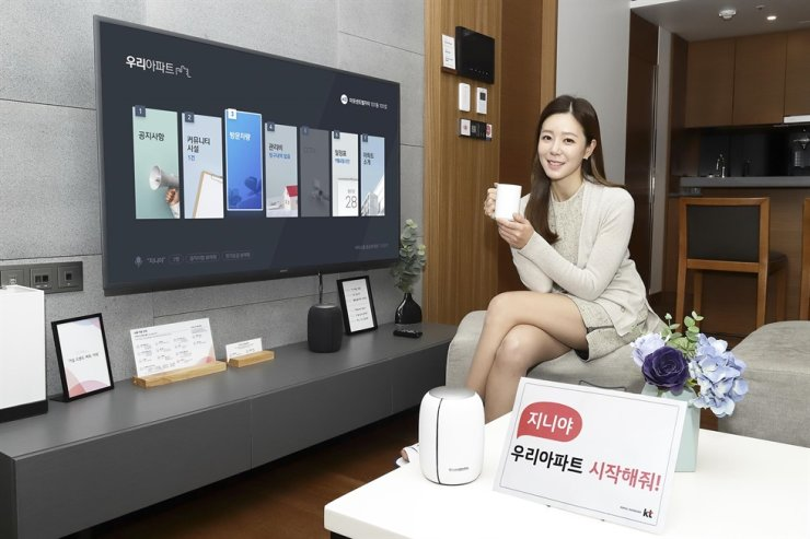 A model promotes KT's Giga Genie artificial intelligence (AI) service installed at an apartment, Wednesday. KT said the AI system allows residents to book community facilities in apartment complexes, check maintenance fees and permit visitor vehicles through voice command. It will begin service at 750 apartment complexes across Korea. Courtesy of KT