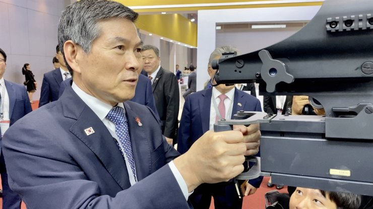 Defense Minister Jeong Kyeong-doo demonstrates a heavy machine gun sight on his visit, Monday, to Defense & Security 2019, held at Bangkok's IMPACT Exhibition and Convention Center. The exhibition will continue until Thursday. Joint Press Corps