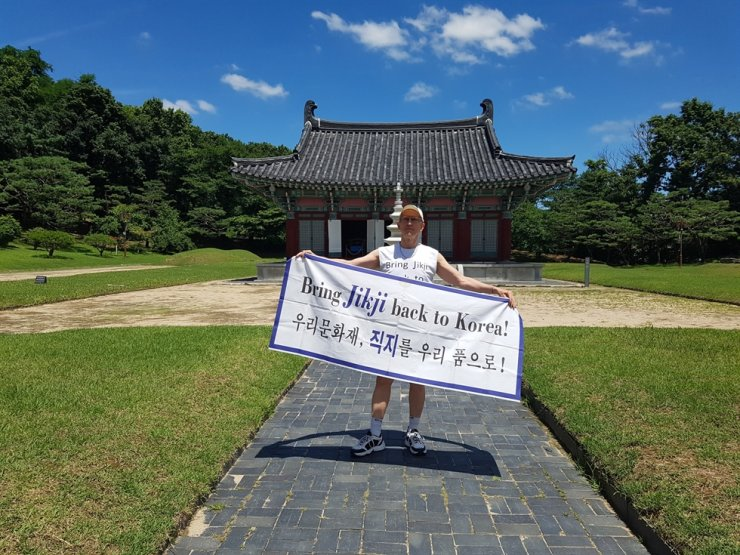 Richard Pennington holds a banner for 'Bring Jikji back to Korea' in front of Heungdeok Temple. Courtesy of Richard Pennington