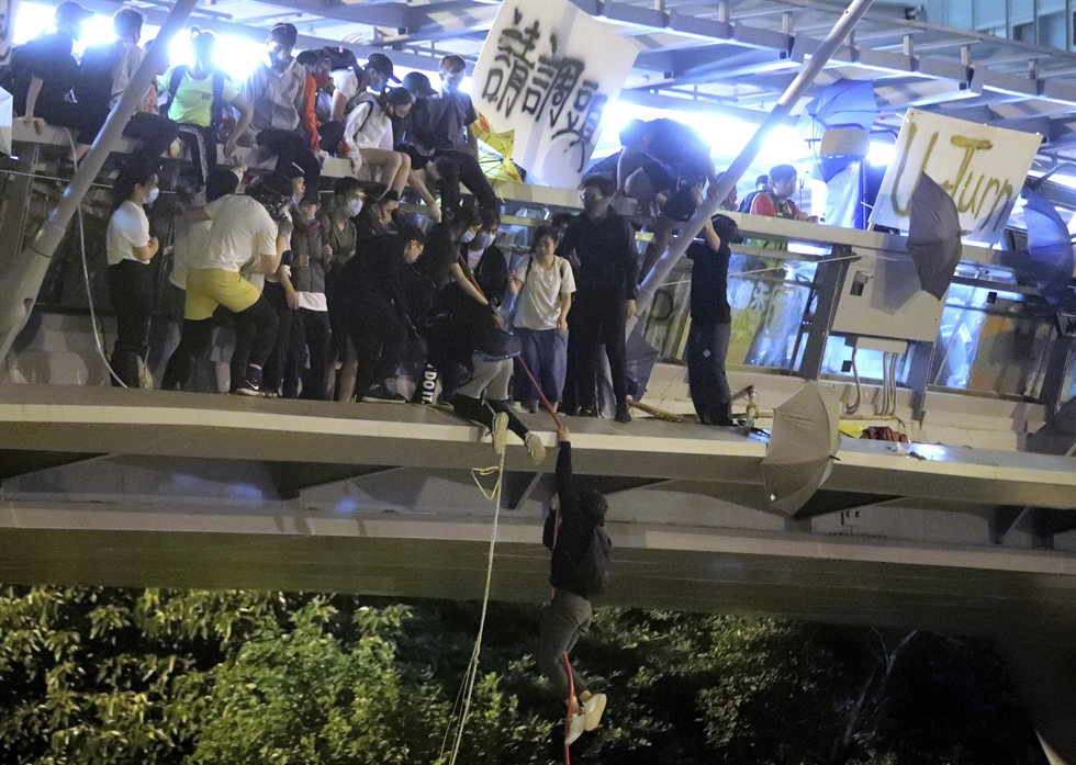 In this Monday, Nov. 18, 2019, photo, riot police detain protesters at Hong Kong Polytechnic University in Hong Kong. About 100 anti-government protesters remained holed up at the university Tuesday as a police siege of the campus entered its third day. (AP Photo/Achmad Ibrahim)